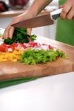 Закройте вверх рук ` s женщины варя в кухне Домохозяйка отрезая свежий салат Вегетарианец и здорово варить Стоковые Изображения RF