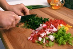 Закройте вверх рук ` s женщины варя в кухне Домохозяйка отрезая свежий салат Вегетарианец и здорово варить Стоковое Изображение RF