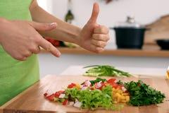 Закройте вверх рук ` s женщины варя в кухне Домохозяйка предлагая свежий салат с большими пальцами руки вверх Вегетарианец и Стоковая Фотография RF