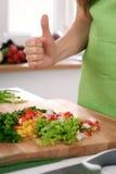 Закройте вверх рук ` s женщины варя в кухне Домохозяйка предлагая свежий салат с большими пальцами руки вверх Вегетарианец и Стоковое фото RF