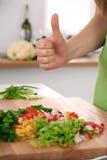 Закройте вверх рук ` s женщины варя в кухне Домохозяйка предлагая свежий салат с большими пальцами руки вверх Вегетарианец и Стоковые Фотографии RF