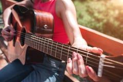 Закройте вверх рук ` s музыканта играя гитару Девушка держит ее пальцы на строках ` s гитары Девушка сидит дальше стоковая фотография rf