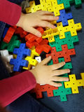 Закройте вверх рук ` s ребенка играя с красочными пластичными кирпичами на таблице Стоковые Фотографии RF