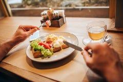 Закройте вверх рук ` s человека держа вилку и нож Плита вкусного waffle с овощами и чашкой чаю таблица стоковое изображение