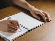 Закройте вверх рук ` s человека писать в тетради помещенной на деревянном des стоковые фотографии rf