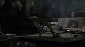 Закройте вверх сварщика женщины или рук кузнеца ремонтируя объект металла с сварочным аппаратом который делает sparkles акции видеоматериалы