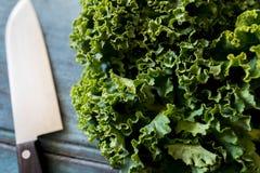 Закройте вверх свежей листовой капусты на деревянном столе с ножом Стоковое Изображение RF
