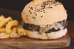 Закройте вверх свежих вкусных фраев бургера и француза Стоковые Изображения