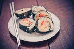 Закройте вверх свернутого риса суш на белом блюде Стоковые Фотографии RF