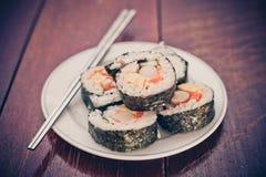 Закройте вверх свернутого риса суш на белом блюде Стоковые Изображения