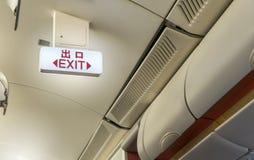 Закройте вверх светлого знака пути аварийного выхода доски на самолете для обслуживаний безопасности Стоковое Фото