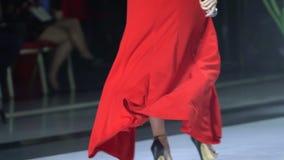 Закройте вверх сексуальных красивых женских ног в ботинках высоких пяток идя в подиум этапа, девушку женщины в красном платье пев сток-видео
