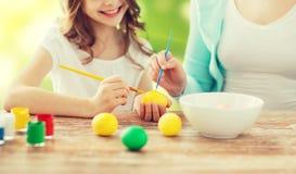 Закройте вверх семьи крася пасхальные яйца Стоковое Фото