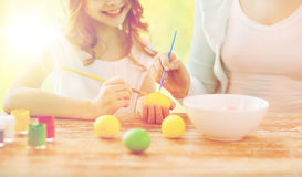 Закройте вверх семьи крася пасхальные яйца Стоковая Фотография RF