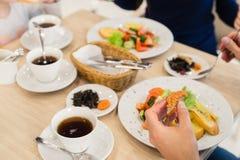 Закройте вверх семьи сидя на таблице наслаждаясь едой Стоковая Фотография RF