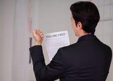 Закройте вверх сердитого молодого бизнесмена нося костюм и держа лист бумаги увольнянного запачканного текста на ем, в Стоковые Фото