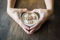 Закройте вверх сердца рук женщины и держать белую чашку кофе с красивым искусством картины Стоковые Изображения RF