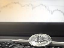 Закройте вверх серебряного Bitcoin на предпосылке диаграммы стоковые фото