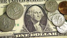 Закройте вверх сияющих монеток на долларовых банкнотах
