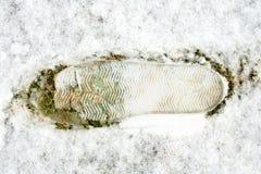 Закройте вверх следа ноги на снеге на зеленой траве Шаг на снеге на зеленой траве Стоковое Изображение