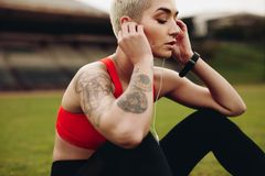 Закройте вверх слушать спортсменки ослабляя музыку стоковая фотография rf