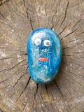 Закройте вверх смешным покрашенного шаржем камня детей голубого с глазами стоковые изображения