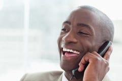 Закройте вверх смеясь над бизнесмена на телефоне Стоковая Фотография