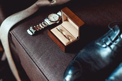 Закройте вверх современных аксессуаров groom обручальные кольца в коричневой деревянной коробке, галстуке, кожаных ботинках и вах Стоковое Изображение RF