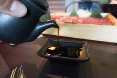 Закройте вверх соевого соуса руки человека лить стоковые изображения rf