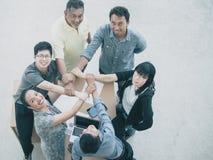 Закройте вверх соединяя рук бизнесмена в предпосылке единства перекрестной обрабатывая стоковое изображение rf