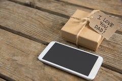 Закройте вверх сообщения на подарочной коробке мобильным телефоном Стоковые Изображения