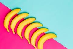 Закройте вверх сочных желтых бананов на предпосылке colorfull голубой и розовой стоковое фото rf