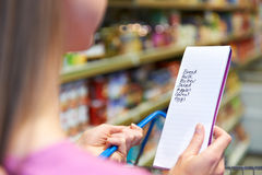 Закройте вверх списка покупок чтения женщины в супермаркете стоковые изображения