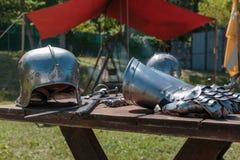 Закройте вверх средневекового серебряного шлема на деревянном столе с Knight& x27; s Стоковые Изображения RF
