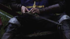 Закройте вверх средневекового солдата очищая его шпагу с травой сток-видео