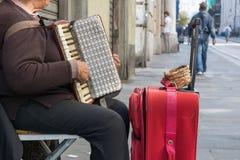 Закройте вверх старой женщины Playng попрошайки грязный аккордеон в Str стоковое изображение rf