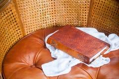 Закройте вверх старой книги с кожей на стуле Стоковое Изображение