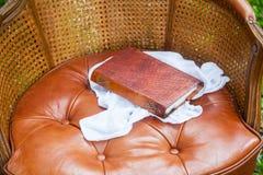 Закройте вверх старой книги с кожей на стуле Стоковые Изображения RF