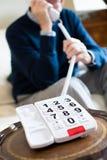 Закройте вверх старшего человека используя телефон с слишком большой кнопочной панелью на Стоковые Фото