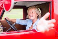 Закройте вверх старшей женщины внутри винтажного грузового пикапа Стоковая Фотография RF