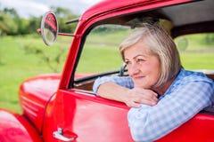 Закройте вверх старшей женщины внутри винтажного грузового пикапа Стоковые Изображения