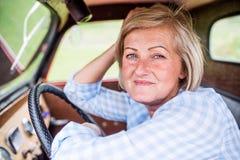 Закройте вверх старшей женщины внутри винтажного грузового пикапа Стоковое Изображение