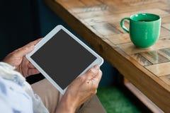 Закройте вверх старшей женщины держа таблетку против кофейной чашки на таблице Стоковая Фотография