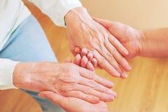 Закройте вверх старшей женщины и молодой женщины держа руки Концепция заботы и поддержки Стоковое фото RF