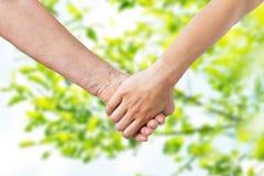 Закройте вверх старшия и молодой женщины держа руки Стоковые Фотографии RF