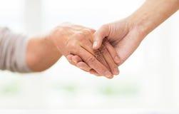 Закройте вверх старшия и молодой женщины держа руки Стоковое фото RF