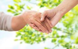 Закройте вверх старшия и молодой женщины держа руки Стоковые Изображения