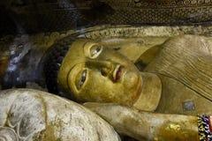 Закройте вверх статуи Будды отдыхая на подушке в пещере на Dambulla Стоковые Фото