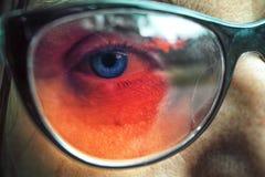 Закройте вверх стекел голубого глаза женщины нося Стоковая Фотография