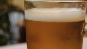 Закройте вверх стекла пива положенного на таблицу акции видеоматериалы